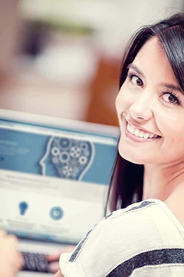 Ung kvinde sidder ved laptop med Newmind website
